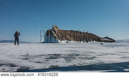 A Picturesque Rocky Island With Unusual Outlines Rises Above A Frozen Lake. At The Foot There Are Ic
