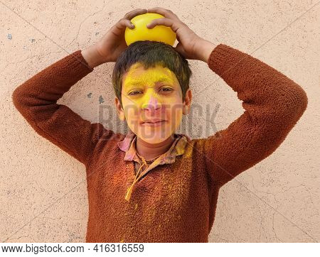Close Up Of A Indian Kid Covered With Colored Holi Powder And He Placed Yellow Balloon On His Head,