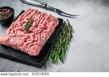 Minced Chicken Or Turkey Raw Meat On Cutting Board With Herbs. White Background. Top View. Copy Spac