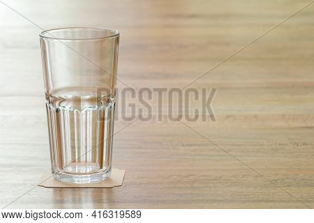 Closeup Empty Glass On Wooden Table, Meaning A Positive Attitude Towards Something And Prompt To Lea