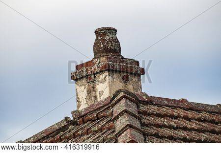 Old Dilipidated Chimney Pot On Tiled Roof In Bad Condition
