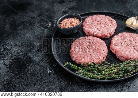 Raw Chicken Turkey Patty, Minced Meat Cutlets On A Plate With Thyme. Black Background. Top View. Cop