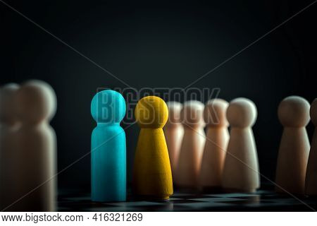 Blue Wooden Dolls For Men And Yellow For Women. Representatives Of The Two Teams Are Facing Each Oth