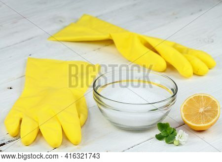 Crystalline Citric Acid And Lemon In A Bowl, Good For Cleaning. Rubber Gloves And Lemon Cut In Half