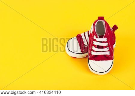 A Pair Of Red Sneakers. Sneakers For A Boy On A Yellow Background. Travel Concept With Kids, Kids Li