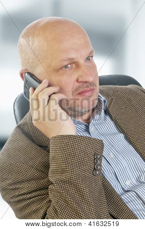 Businessman Talking On The Phone Sitting In A Chair.
