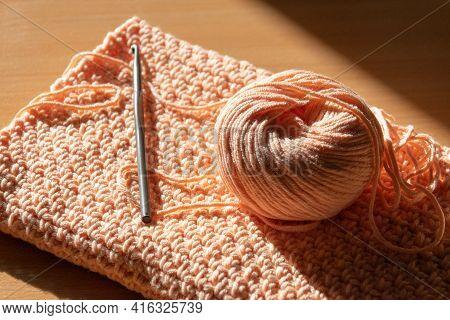 Crochet Hook And Ball Of Yarn On Crocheted Fabric