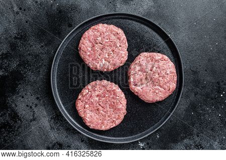 Raw Chicken Turkey Patty, Minced Meat Cutlets On A Plate With Thyme. Black Background. Top View