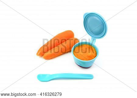Baby First Solids. Weaning. Homemade Vegetable Carrot Puree In A Small Container With A Spoon