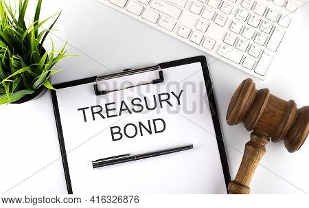 White Office Desk Table With Blank Sheet With Text Treasury Bond , Keyboard And Gavel,