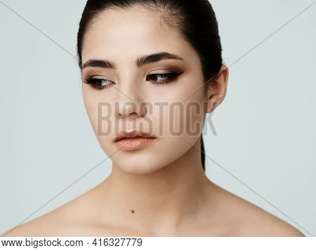 Pretty Woman With Bare Shoulders Face Makeup Side Glance Close-up