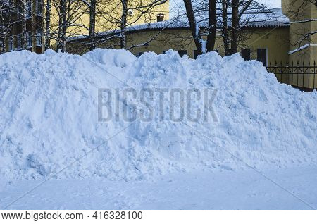 Large Piles Of Snow On The Side Of The Road For Cars. High Drifts After A Snowfall Or Blizzard