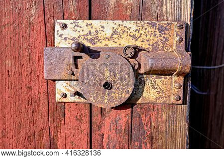 Old Lock Sitting On A Red Barn Door