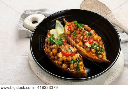 Stuffed Sweet Potato With Spiced Chickpea, Dressing And Herbs.