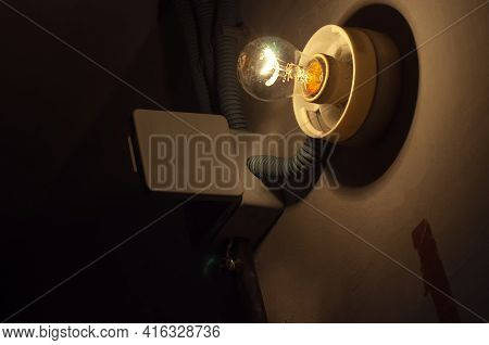 Wall Of Dark Old Basement Corridor With Glowing Incandescent Lamp
