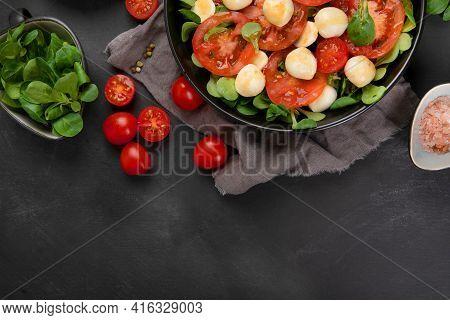 Delicious Italian Caprese Salad With Sliced Tomatoes And Mozzarela On Dark Background.