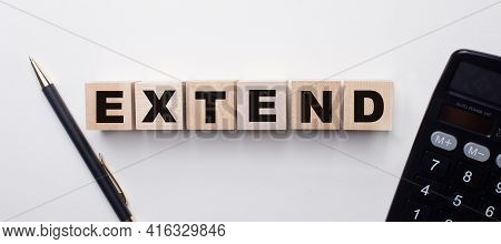 On A Light Background Between The Calculator And The Pen There Are Wooden Cubes With The Word Extend