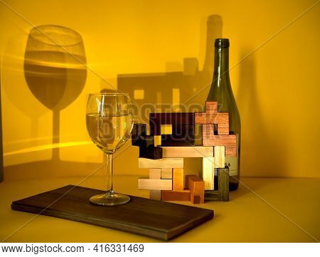 A Glass Of White Wine, On A Yellow Background With An Abstract Pattern,the Play Of Chiaroscuro Empha
