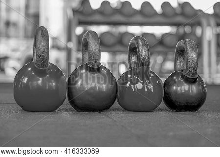 Black Kettlebells In A Row In A Gym. Several Black Weights Different Weights. Black Metal Weights Ke