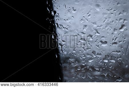 A Contrasting Background Of Black Wall And Fogged Rain-soaked Glass.
