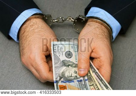 Hand Of Businessmanin Handcuffs Holding Dollar Banknotes. Office Clerk Man In Handcuffs With A Bribe