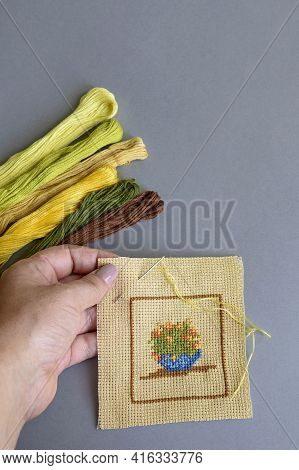 Close Up Of Woman's Hand Making Cross-stitch On Light-brown Cotton Canvas. Handmade Embroidery, Set