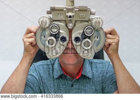 Male Checks His Vision On The Machine Checking Patient Vision At Eye Clinic Or Optics Store