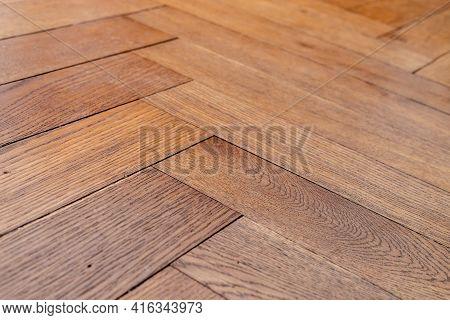 Low Angle Photo Of Orange Brown Aged Hardwood Oak Tile Floor Of Herringbone Flooring. Hundred Years
