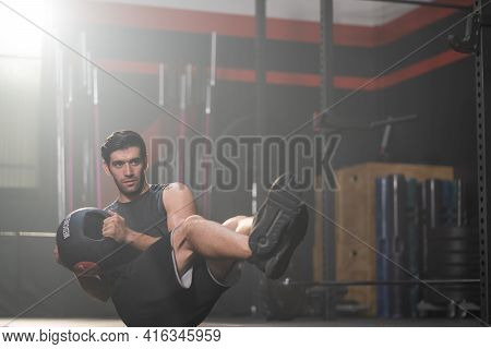 Handsome Adult Caucasian Men Using Weight Ball To Do Crossfit Exercise Inside Of Fitness Gym To Work