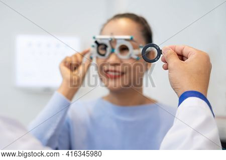 Selective Focus At Women Face. While Doctor Using Optometry Equipment And Trial Glasses Frame  To Ex