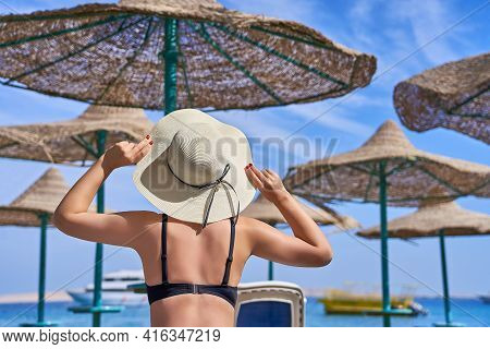 A Beautiful Girl In A Swimsuit Looks At The Sea And Holds On To A Hat. Summer Vacation On The Sea Be