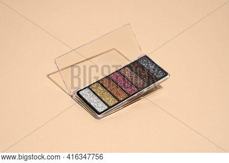 Make-up Palette Floating Over A Beige Background. Professional Multicolor Eye Shadow Make-up Palette