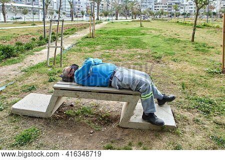 Antalya, Turkey - March 20, 2021: Municipal Worker, Wearing Face Mask, Sleeps On Bench In  Public Pa