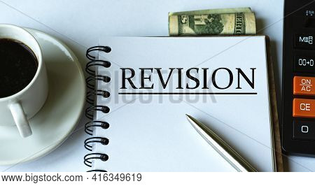 Revision - Word Written In A Notebook Against The Background Of A Calculator, Money And A Cup Of Cof