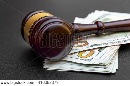Judge's Gavel With Money On A Black.