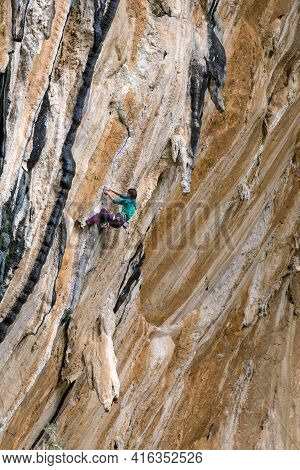 A Woman Climbs A Rock On A Colony. A Slender Girl Overcomes A Difficult Climbing Route. A Climber Tr