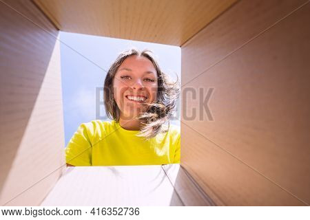 Happy Smiling Woman Unpacking Box. Satisfied Client Woman Unboxing Delivery Package. View From The B