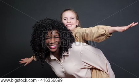 Stylish Black Stepmother In White Blouse Holds On Backs Adopted Schoolgirl With Fair Hair Raising Ha