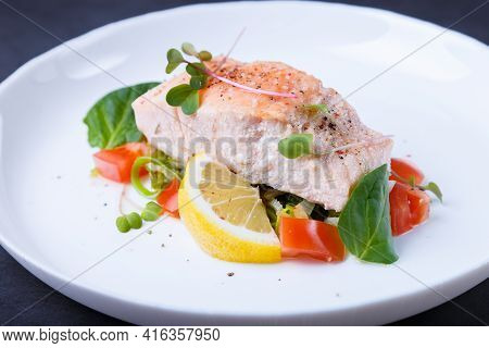 Trout (salmon) With Vegetables, Lemon And Microgreens, Cooked By The Confit Method. Traditional Fren
