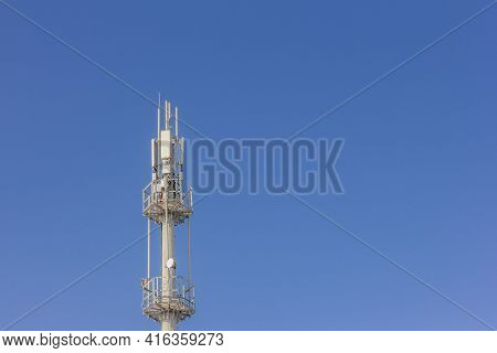 Cell Tower Transmitting Signals Of Mobile Phone And Internet Against The Blue Sky
