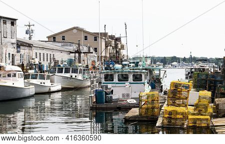 Portland, Maine, Usa - 20 July 2019: Commercial Fishing Boats Docked In A Canal With Colorful Lobste