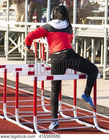 Rear View Of A High School Girl Wearing Headphones While Warming Up Doing Hurdle Drills On An Outdoo