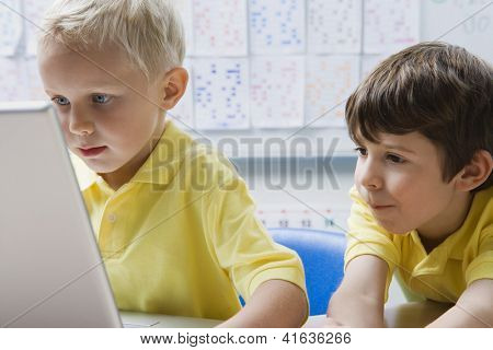 A preadolescent boy using laptop while friend looking at it in classroom