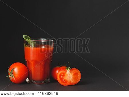 Tomato Juice In A Glass With Fresh Tomatoes On Dark Background