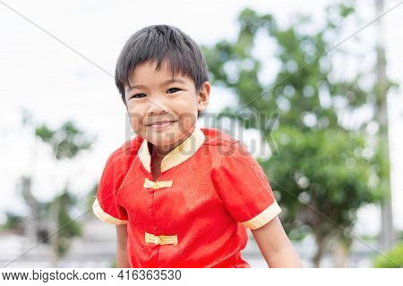 Portrait Of Smiling Face Asian Child Boy. He Wearing A Red Shirt. At The Park Or Play