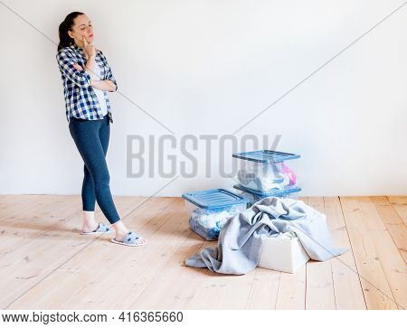 A Woman Looks At Containers With Seasonal Clothes And Things, Is Going To Put Everything In Its Plac