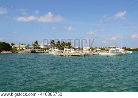 GRAND CAYMAN, CAYMAN ISLANDS - DEC 23, 2012: Boat docks and homes seen from the water along the coast line of .