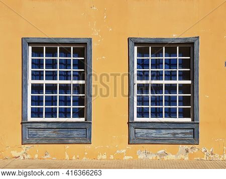 Traditional Guillotine Windows In Historic Colonial House. Two Old Style Blue Wooden Windows On A Br