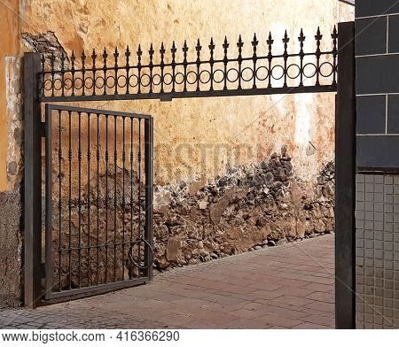Old Iron Fence With Open Door And Uncorked Concrete Wall. Close Up Of Exterior Metal Enclosure. Lock