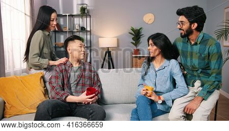 Portrait Of Joyful Young Mixed-races Family Couples Talking And Laughing Gathered Together. Asian An